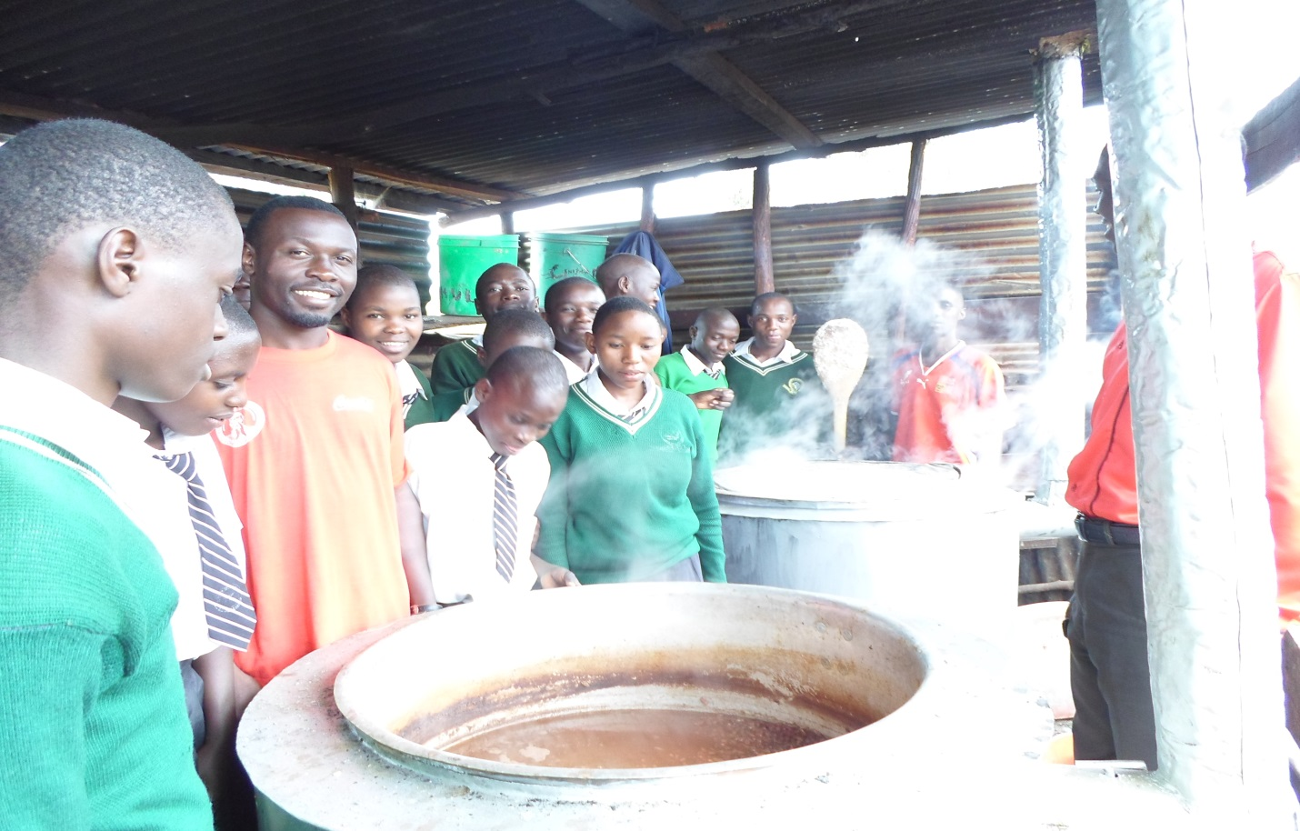 Teachers and Students being happy at the sight of Large Clean Cooking Stoves